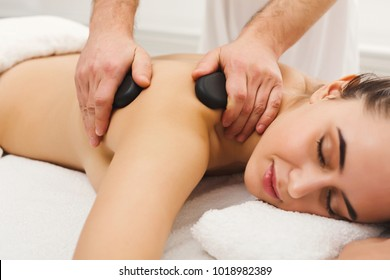 Beautiful woman getting hot stones arm massage in spa salon. Beauty treatment therapy, wellness and relaxation concept