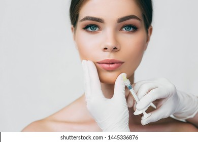 beautiful woman getting injection in her mouth for lip augmentation. Procedure make lips bigger