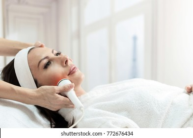Beautiful woman getting laser and ultrasound face treatment in medical spa center, skin rejuvenation concept