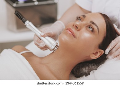 Beautiful woman getting microcurrent therapy session for her neck and face skin. Attractive woman smiling, getting skincare treatment at cosmetology clinic. Beauty, rejuvenation concept