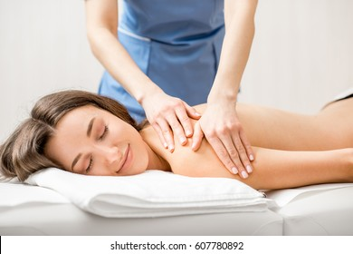 Beautiful woman getting professional massage on her back lying on the couch in the Spa