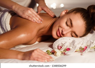 Beautiful woman getting relax massage in spa center with orchids nearby