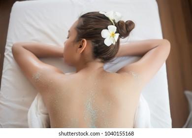 Beautiful woman getting a salt scrub beauty treatment in the health spa.