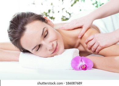 Beautiful woman getting shoulder massage at spa salon