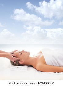Beautiful woman is getting spa treatment over the sea and sky background