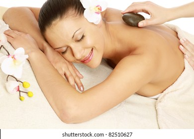A beautiful woman getting stone therapy in a spa center