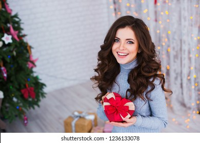 Beautiful woman with a gift on Christmas Eve. Festive mood.