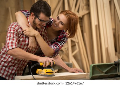 Beautiful woman with ginger hair hugging and smiling to his man while he working with wood. Talented joiner machining timber using electric sander.Couple standing and posing in carpenter's shop.