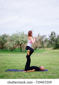 Beautiful woman and girl practise yoga pose outside. Women doing stretching workout in park outdoors at sunset.