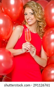 Beautiful woman with a glass of champagne. Holiday balloons.