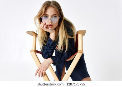 beautiful woman in glasses leaned on a chair fashion