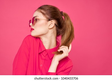 beautiful woman in glasses on a pink background
