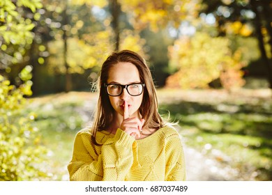 Beautiful woman in glasses with secret holding finger over lips over autumn yellow background Closeup portrait of long hair girl