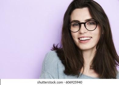 Beautiful woman in glasses smiling in studio