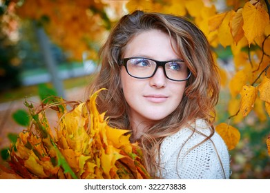 Beautiful woman with glasses walks in autumn park.