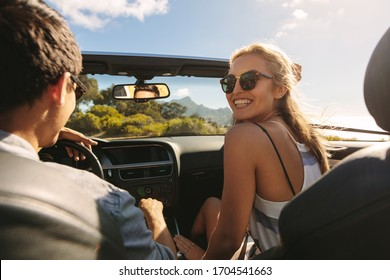 Beautiful woman going on a roadtrip with her boyfriend. Couple going on a long drive in a convertible car.