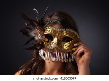 Beautiful woman with gold carnival mask on dark background