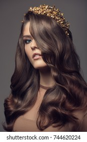 Beautiful woman in gold crown on her head. Long wavy brown hair.