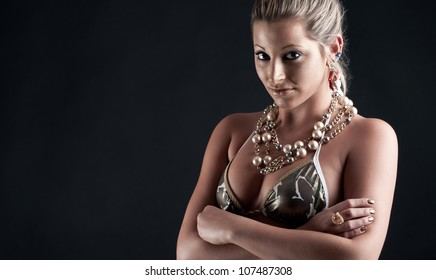 Beautiful woman with golden make up and bikini against black background.
