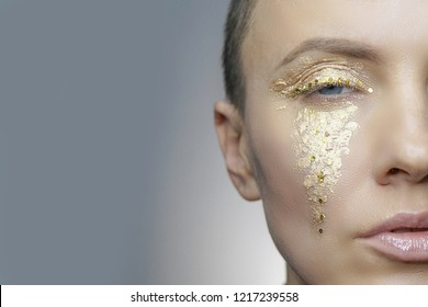 Beautiful woman with golden makeup like tears, detail, side face