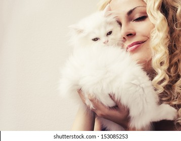 Beautiful woman golding fluffy white Persian kitten