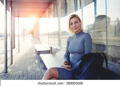 Beautiful woman in good mood looking at camera while waiting for a call on her cell telephone, pretty female using smart phone while sitting on a bus stop against sun rays background with copy space
