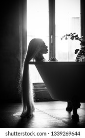 A beautiful woman with gorgeous long blond hair is relaxing in the bath. Silhouette of a woman in profile lying in the bathroom