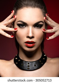 Beautiful woman in gothic style, evening makeup and red nails with thorns.