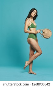 Beautiful woman in a green bathing suit with a beach bag needles