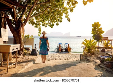Beautiful woman in green drees on the tropical beach of Phi Phi island at sunset in Southern Thailand. Travel magazine concept.