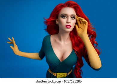 Beautiful woman in green superhero costume posing at camera on blue background