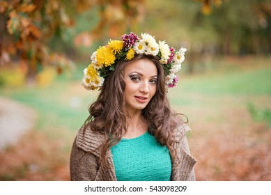 Beautiful woman in green with a yellow wreath posing in autumnal park. Young brunette woman spending time in the autumn of near a tree in the forest. Long dark hair smiling attractive woman.