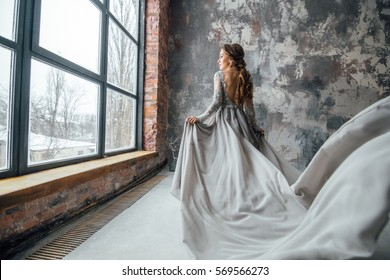 Beautiful woman in grey evening dress with plume in loft interior.