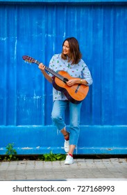 beautiful woman with a guitar near the blue wall. fashion, style, music