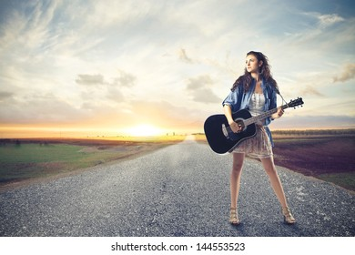 beautiful woman with a guitar on a deserted road