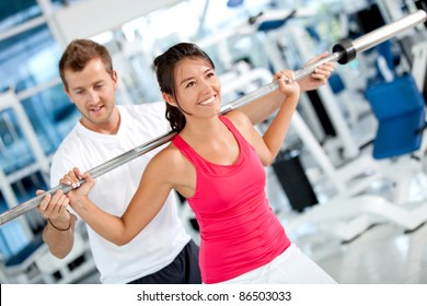 Beautiful woman at the gym exercising with her trainer