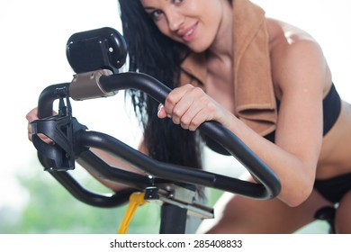 Beautiful woman at the gym on bike