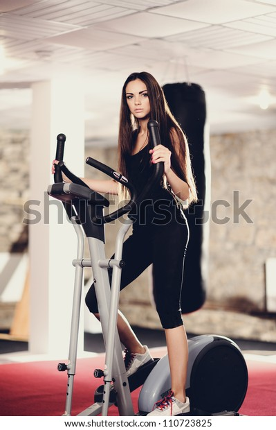 beautiful woman at the gym on stationary bicycle