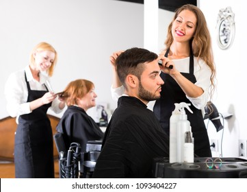Beautiful woman hairdresser is cutting hair on a handsome man client in a hair styling salon indoors. Focus on man