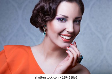 beautiful  woman with hairstyle posing in studio with jewerly, close up portrait