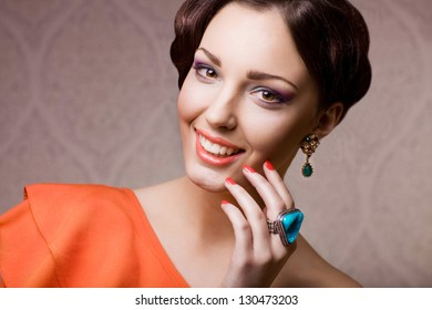 beautiful woman with hairstyle posing in studio with jewelry, close up portrait
