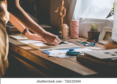 Beautiful woman hand crafting book at the tabletop with stationery. Stylish craftswoman with stationery work at his hipster workstation.