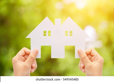 beautiful Woman hand holding paper house on nature bright background