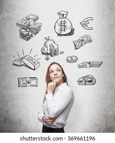 beautiful woman with hand on chin looking up and thinking about money, black pictures symbolizing money over her head. Concrete background. Front view. Concept of running into money.