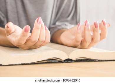 beautiful woman hand praying peaceful in church with bible book on desk