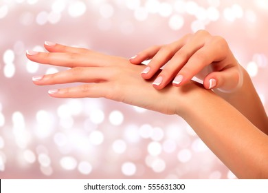Beautiful woman hands against an abstract background with blurred lights