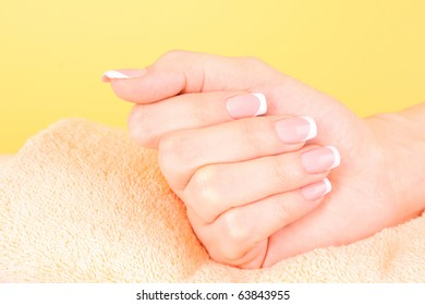 Beautiful woman hands with french manicure on yellow background