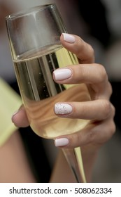 Beautiful woman hands with gel manicured nails holding a glass of champagne