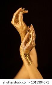 Beautiful woman hands gold, golden hands, glitter posing like ballet dancer, sensual studio shot