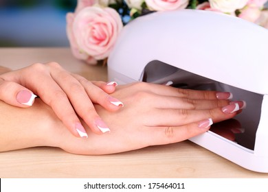 Beautiful woman hands and lamp for nails on table close up